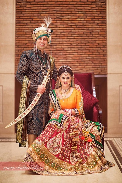 Red wedding lehenga, embellished with gotta patti motifs and foral embroidery, styled with orange raw silk choli and green dupatta