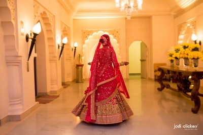 Pink bridal flared lehenga embellished with double style dupatta,  gold sequined motifs and polki necklace set by Sabysachi Mukherjee