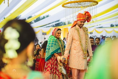 Dressed in complementing peach and red wedding outfits for their wedding ceremony held at I-lawns, Wadala