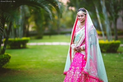 Bride Jeenal looking beautiful in this pink and turquoise blue gotta patti Bridal Lehenga.