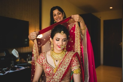 Adorned in regal red and gold Sabyasachi lehenga paired with stunning gold and kundan jewellery for the wedding day.