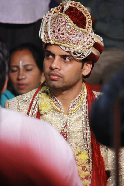 Wedding attire for groom adorned with  gold chain