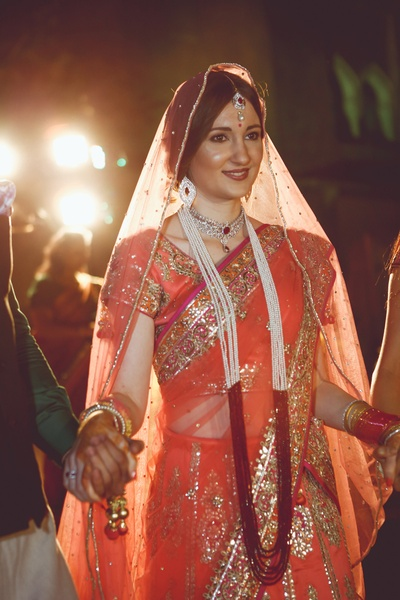 Wedding lehenga embellished with thread worked embroidered motifs, gota pati work and multi-strand raani haar in place of a garland