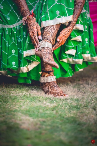 Feet mehendi paired with silver bridal jewellery and a contrast green lehenga