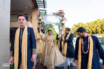 the bride entering under a phoolon ki chadaar with her brothers