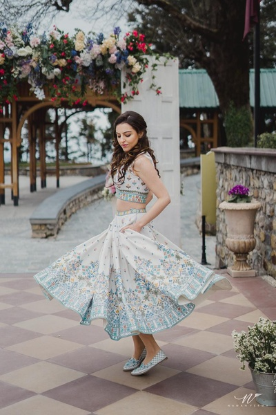 The bride twirling in a classic Anita Dongre skirt and crop top at her pre wedding carnival themed brunch