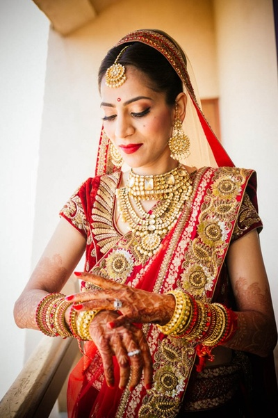 Mridula wearing red lehenga with heavy gold embroidery and zari work and heavy gold polki jewellery for the wedding ceremony.