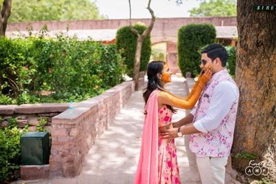 Bride and groom pose together during the haldi function at  Bal Samand Lake Palace, Jodhpur