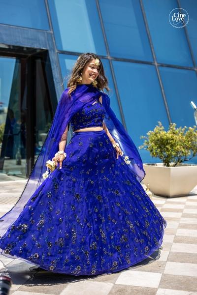 The bride looks gorgeous in an indigo embellished lehenga.