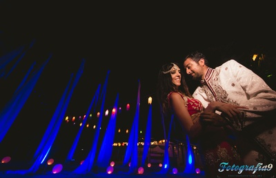 Romantic post- wedding photo shoot with dramatic backdrop of drapes, globe lights and lanterns