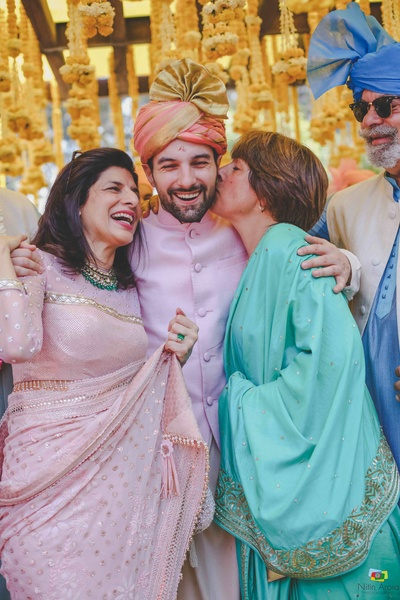 The groom posing with his mother  and mother-in-law during the baraat