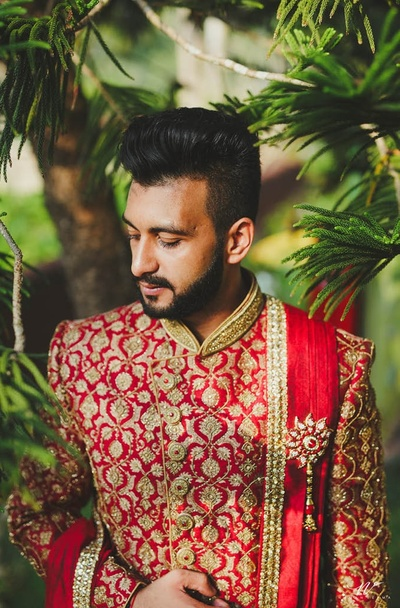 the groom looking handsome in a red sherwani