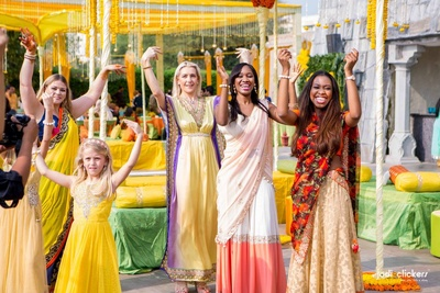 Wedding guests dressed in pretty hues of yellow for the yellow, orange and pista green themed mehendi ceremony held at Hotel Fairmont, Jaipur