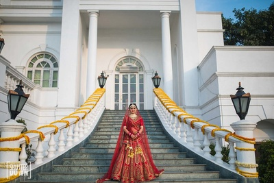 Traditional bride poses in her classic red JJ Valaya lehenga for her wedding at Hotel Renaissance, Lucknow
