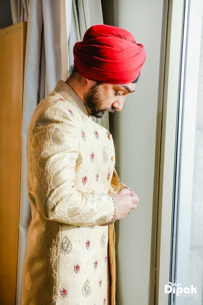 Groom Sandeep gets ready for the wedding ceremony in his embroidered sherwani