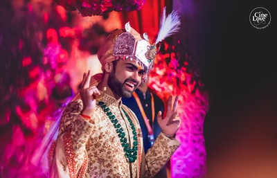 The groom looks dapper in this cream sherwani with gold embroidery, paired with an emerald necklace.