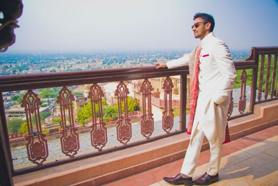 Ivory classic achkan with matching churidaar an maroon formals, styled with red woven angavastram and red pocket square