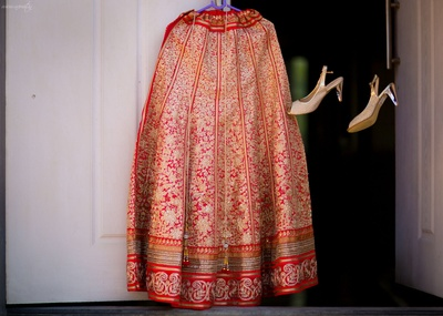 Kalidaar red lehenga beset with heavy and intricate embroidery, embellished with zari border layers