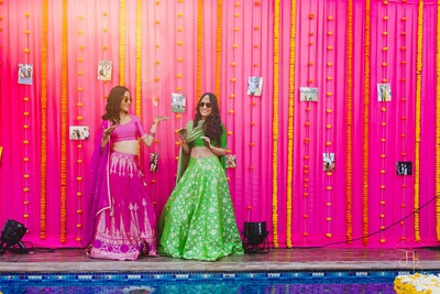 The bride with her sister posing against a background of pink cloth & genda phool decor