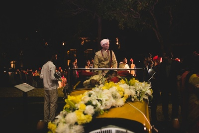 Dashing groom entering the wedding ceremony in a vintage car decorated with flowers.