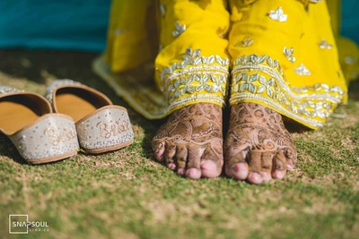 A closer look at Niharika's mehendi-adorned feet and adorable jootis with the word 'Bride' on them.