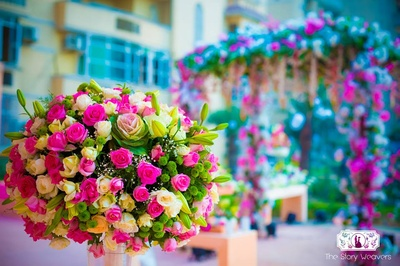 Floral centerpiece bouquet made with pink and yellow roses along with fresh green ferns and buds
