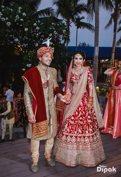 The couple looks stunning in these beautiful red and gold outfits