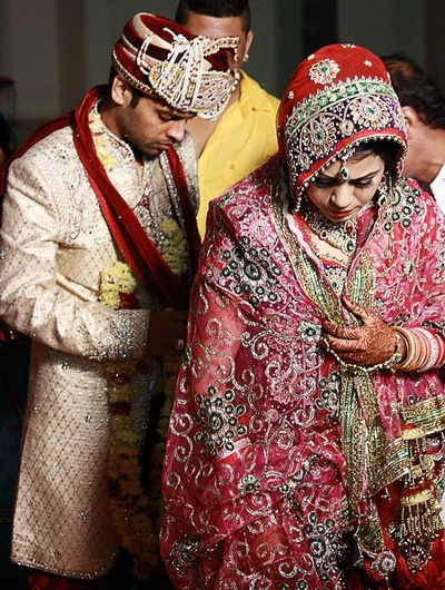 Bride adorning a sheer pink dupatta embellished with silver sequins featuring a floral pattern