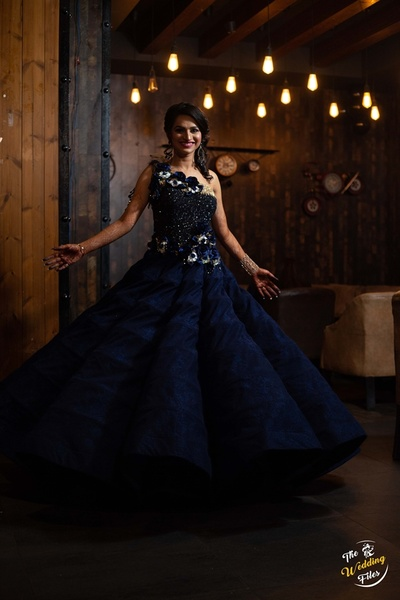 the pretty bride twirling in a navy blue gown at her cocktail ceremony