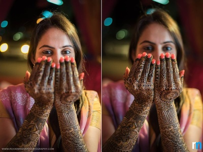 Arms covered in intricately patterned mehendi design, adorned with coral manicured nails