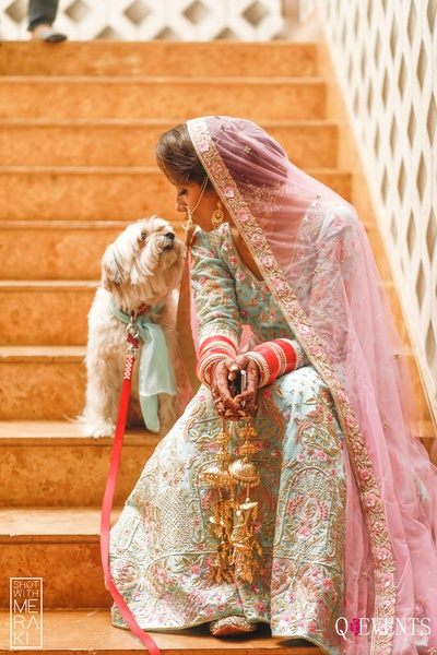 Traditional bride posing with her dog for candid click