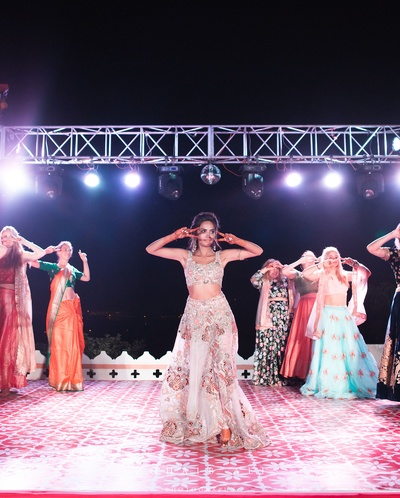 bride with bridesmaids dance performance for the sangeet ceremony
