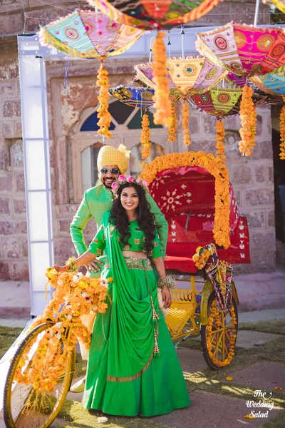 The couple twinning in green while possing in front of a decorated cycle rickshaw.