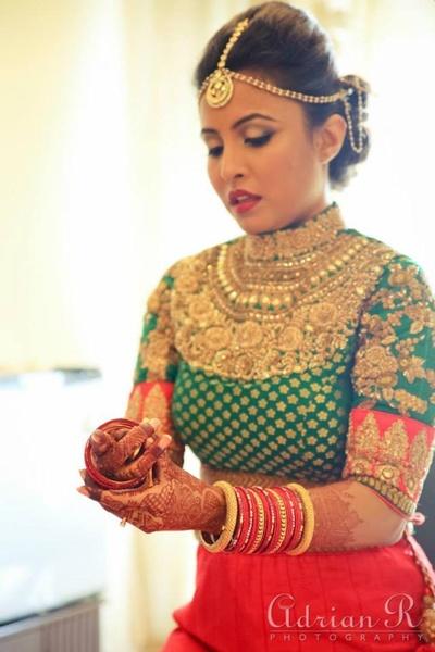 Orange lehenga styled with green high necked gold embellished blouse