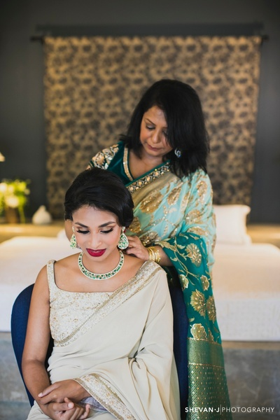 mother of the bride helping her to get ready for the wedding ceremony