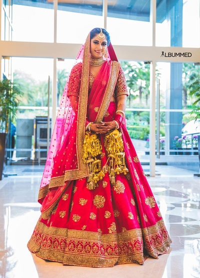 Dressed up in a pretty pink and gold bridal lehenga by Sabyasachi for the wedding held at Amaanta farms.