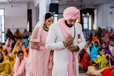 a candid capture of the bride and groom during the wedding ceremonies at the gurdwara