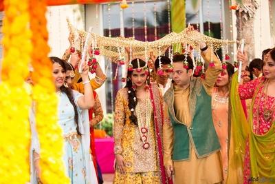 Bridal entry under floral chaadar for mehendi ceremony.