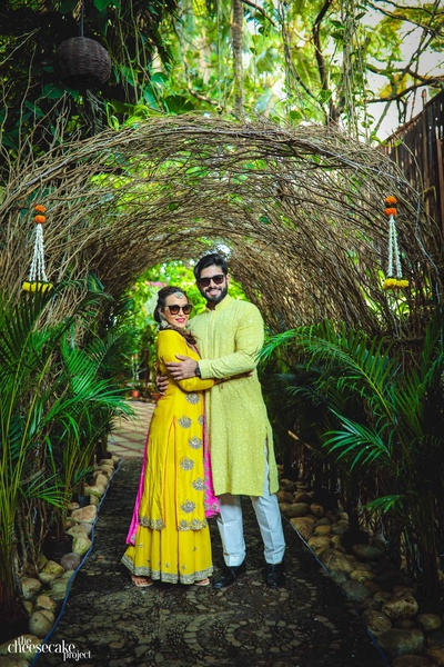 quirky couple poses for their photoshoot with shades and style