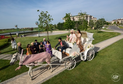 The groom entering the wedding venue on a white horse-driven chariot.
