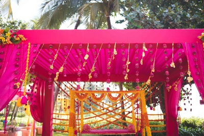 Deep pink drape decor paired with fresh genda phool for the mehendi day!