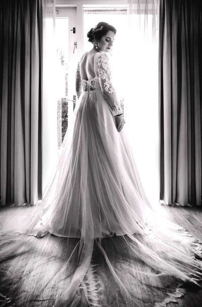 Blak and white image of the bride getting ready in her white gown for the christian ceremony