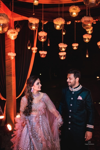 The bride flaunts a beautiful lehenga with pretty ruffles, while the groom looks dapper in his sherwani!