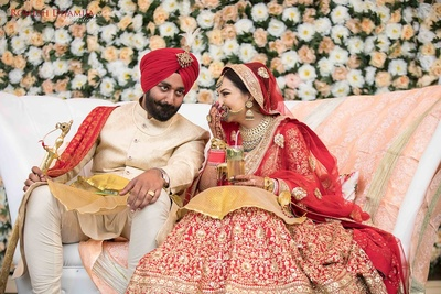 Deep wearing beige and gold sherwani styled with red turban complementing the bride in red and gold wedding lehenga.