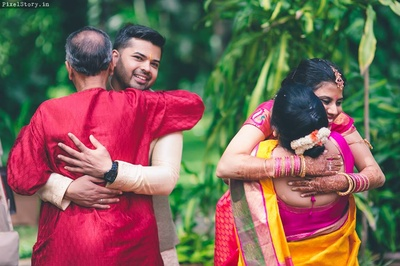 Pratibha and Ashwin hugging their parents after the wedding ceremony captured beautifully by PixelStory.in