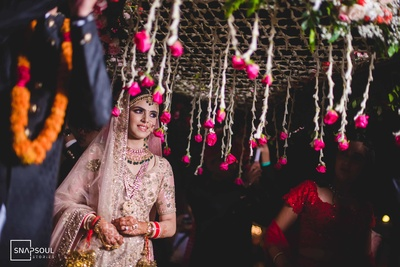 The bride is entering with a quintessential phoolon ki chaadar over her!