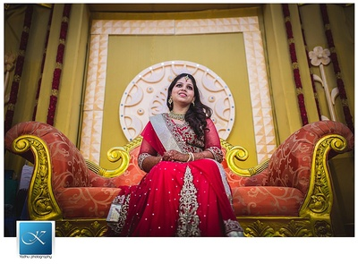 Red monochrome lehenga with gold lace, cut work embellishments and stones for the reception ceremony