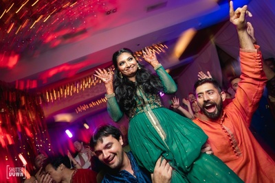 a candid picture of the bride dancing and having a blast at the sangeet