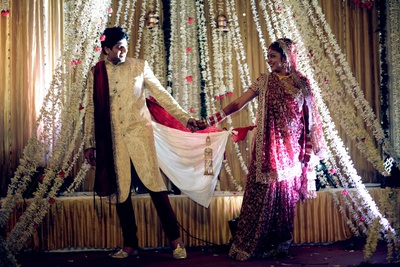 Cream and gold damask patterned bandhgala sherwani paired with a maroon churidaar and crushed dupatta