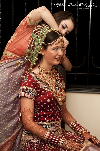 Bride dressed in traditional Indian wedding attire with gold jewellery and chooda set